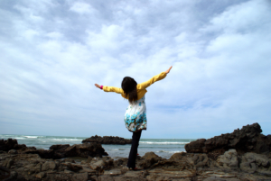 Image of woman standing with her arms outstretched facing the ocean